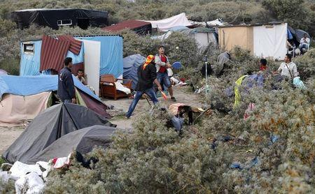 """Migrants play paddle ball near tents in the makeshift camp called """"The New Jungle"""" in Calais"""