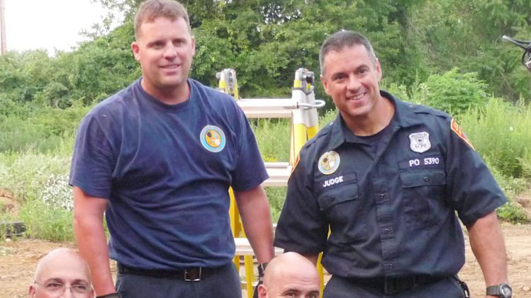 In this image released by the Suffolk County Police Department, Thursday, Aug. 2, 2012, officers pose for a photo with a young deer before releasing it in Mount Sinai, N.Y. Landscapers called police after seeing that the fawn had fallen into a 20-foot-deep manhole. (AP Photo/Suffolk County Police Department)