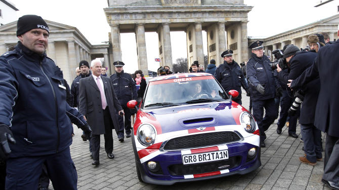 Members of the British royal family, Princess Beatrice of York, left, and Princess Eugenie of York, right, are protected by the police as they drive a car during a promotion event for the Great Britain MINI Tour 2013 at the Brandenburg Gate in Berlin, Germany, Thursday,Jan.17, 2013. It was meant to be a Mini adventure that nearly became a major embarrassment. Two British royals on a mission to promote their country broke German road rules by running a red light near Berlin's iconic Brandenburg Gate. With photographers and police in tow, Princess Eugenie and her older sister Princess Beatrice then took a swift right into the safety of the British embassy compound. At least the 22 and 24-year-old sisters didn't have to decide which side of the road to drive on. The entire 500-meter (550-yard) staged tour was along one-way streets (AP Photo/Michael Sohn)