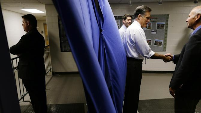 A U.S. Secret Service agent, left, stands watch as Republican presidential candidate and former Massachusetts Gov. Mitt Romney and his vice presidential running mate Rep. Paul Ryan, R-Wis., greet supporters during a photo line backstage before the start of a campaign rally at Koehler Athletic Complex, University of Findlay, Sunday, Oct. 28, 2012, in Findlay, Ohio. (AP Photo/Charles Dharapak)