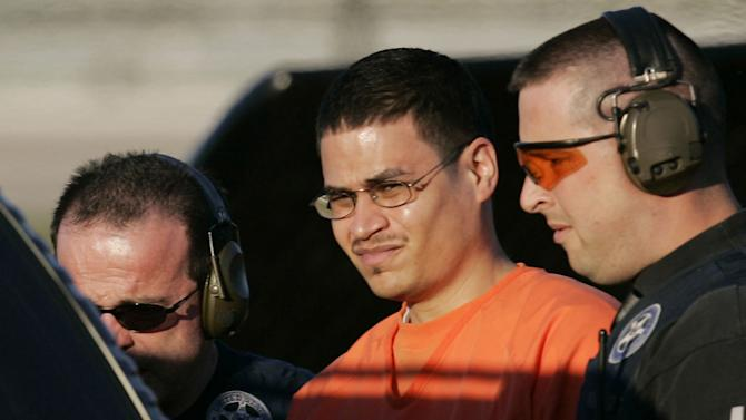 """FILE - In this Jan. 5, 2006 file photo, Jose Padilla, center, is escorted to a waiting police vehicle by federal marshals near downtown Miami. The American Civil Liberties Union says it will ask the OAS' human rights commission to investigate the U.S. government for allegedly violating the rights of convicted terrorism plotter Jose Padilla by labeling him an """"enemy combatant"""" a decade ago and subjecting him to interrogation that amounted to torture, including sleep and sensory deprivation in solitary confinement. (AP Photo/J. Pat Carter, File)"""