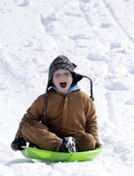 Jayden McQueen, 7, sleds down the hill at the overpass at K-61 and Avenue A on Tuesday morning, Feb. 26, 2013, in Hutchinson, Kan. For the second time in a week, a major winter storm paralyzed parts of the nation's midsection Tuesday, dumping a fresh layer of heavy, wet snow atop cities still choked with piles from the previous system and making travel perilous from the Oklahoma panhandle to the Great Lakes. (AP Photo/The Hutchinson News, Lindsey Bauman)