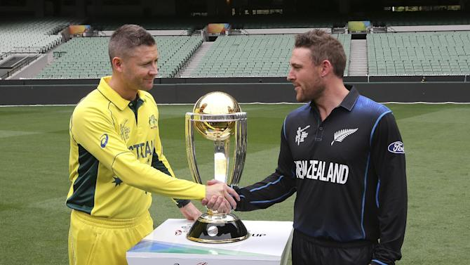 Australia's captain Michael Clarke, left, and New Zealand's captain Brendon McCullum shake hands as they pose for a photo with the Cricket World Cup trophy at the MCG in Melbourne, Australia, Saturday, March 28, 2015. New Zealand will tackle Australia  in the Cricket World Cup final Sunday.(AP Photo/Rob Griffith)