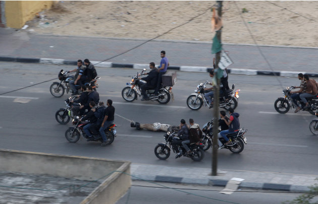 Palestinian gunmen ride motorcycles as they drag the body of a man who was killed earlier Tuesday as a suspected collaborator with Israel, in Gaza City, Tuesday, Nov. 20, 2012. The man was one of six