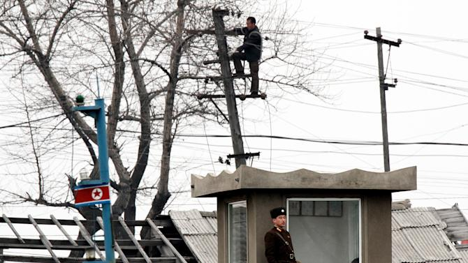 In this Wednesday March 6, 2013 photo, a North Korean man works atop a utility pole as a soldier man on a post along the river bank of the North Korean town of Sinuiju, opposite side of the Chinese border city of Dandong. The U.N. Security Council responded swiftly to North Korea's latest nuclear test by punishing the reclusive regime Thursday with tough, new sanctions targeting its economy and leadership, despite Pyongyang's threat of a pre-emptive nuclear strike on the United States. (AP Photo) CHINA OUT