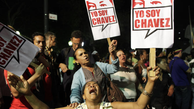"A supporter of Venezuela's President Hugo Chavez cries as she holds a sign that reads in Spanish ""I am Chavez"" as Chavistas gather in Bolivar square to mourn Chavez's death in Caracas, Venezuela, Tuesday, March 5, 2013. Venezuela's Vice President Nicolas Maduro announced that Chavez died on Tuesday at age 58 after a nearly two-year bout with cancer. During more than 14 years in office, Chavez routinely challenged the status quo at home and internationally. He polarized Venezuelans with his confrontational and domineering style, yet was also a masterful communicator and strategist who tapped into Venezuelan nationalism to win broad support, particularly among the poor. (AP Photo/Ariana Cubillos)"