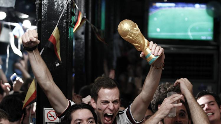 German fans celebrate after watching the FIFA World Cup Brazil 2014 final match between Germany and Argentina at a pizzeria in Buenos Aires on July 13, 2014