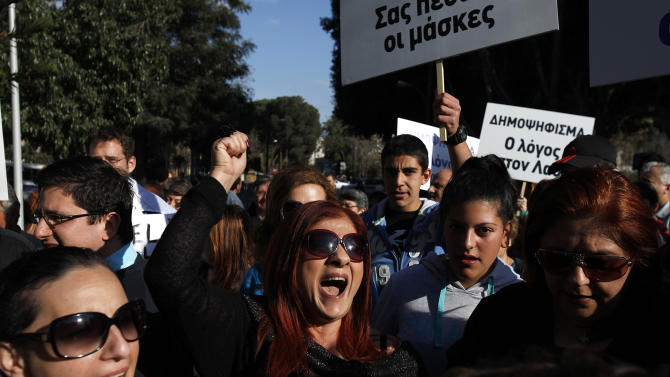 Protesters shout slogans during a protest outside of the parliament in Nicosia, Cyprus, Monday, March 18, 2013. A vote on a bailout package for Cyprus that includes an immediate tax on all savings accounts has been postponed until Tuesday evening. Yiannakis Omirou, the speaker of Parliament, said the delay was needed to give the government time to amend the deal reached over the weekend that prompted an outcry from those who thought their money was safe. In order to get euro 10 billion ($13 billion) in bailout loans from international creditors, Cyprus agreed to take a percentage of all deposits — including ordinary citizens' savings — an unprecedented step in Europe's 3 ½-year debt crisis. (AP Photo/Petros Karadjias)