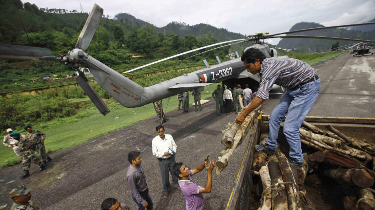 Locals unload woods from a truck to be loaded on to an Indian Air force helicopter, in Gauchar, in northern Indian state of Uttarakhand, Tuesday, June 25, 2013. Truckloads of wooden logs and clarified butter were loaded onto air force transport planes and flown to the temple town of Kedarnath to conduct a mass funeral for the flood victims, an air force official said. Authorities began preparations to cremate the bodies of hundreds of people who perished in monsoon flooding. (AP Photo/Rafiq Maqbool)