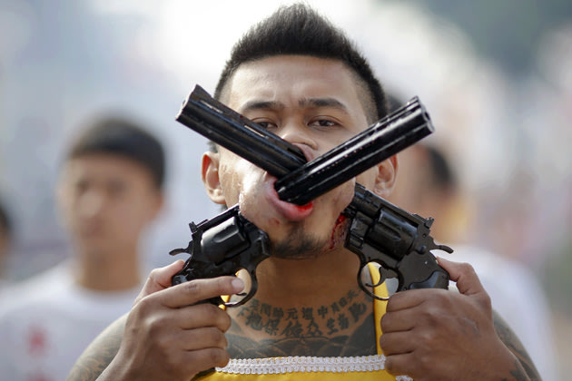 A devotee of the Chinese Bang Neow Shrine with two guns pierced through his cheeks takes a part in procession during the annual vegetarian festival in Phuket