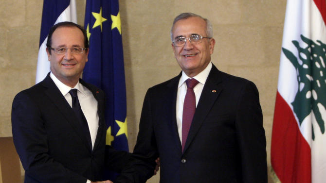 """Lebanese President Michel Suleiman, right, shakes hands for photographers with French President Francois Hollande, left, at the Presidential Palace in Baabda, east of Beirut, Lebanon, Sunday, Nov. 4, 2012. Hollande said France will stand against instability in Lebanon. Hollande's comments during a short visit to Beirut come as many in Lebanon fear that Syria's civil war could spill over. Speaking to reporters after meeting President Michel Suleiman, Hollande said that amid Syria's civil war, """"we are committed to give you guarantees regarding security, stability and the unity of Lebanon.""""  A top anti-Syrian intelligence chief was killed in a car bomb in Beirut last month. The assassination stirred up deadly sectarian tensions in Lebanon, where Sunnis and Shiites are deeply divided over the Syrian civil war, raising the specter of renewed sectarian fighting. (AP Photo/Bilal Hussein)"""