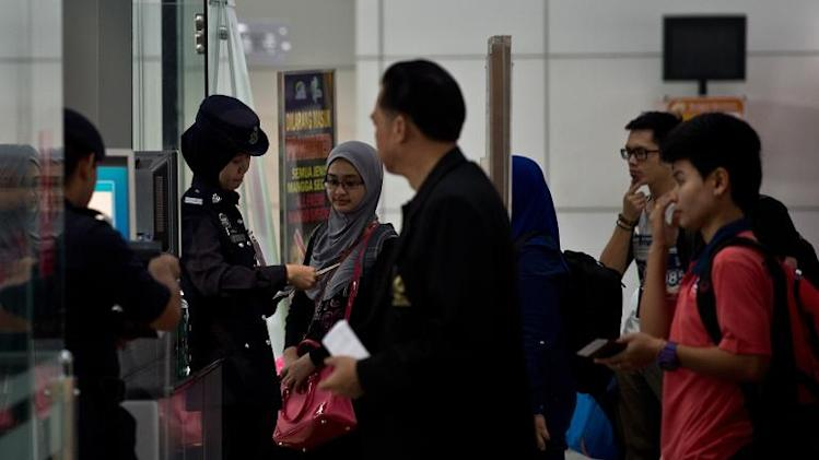 Malaysian police check passports of passengers in the departure hall of Kuala Lumpur International Airport in Sepang on March 10, 2014