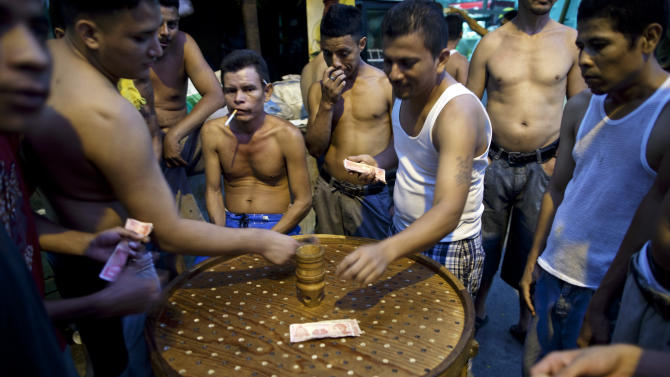 """In this May 3, 2012 photo, inmates make bets as they play a game of """"Chingolingo"""" in San Pedro Sula Central Corrections Facility in San Pedro Sula, Honduras. Inside one of Honduras' most dangerous and overcrowded prisons, inmates operate a free-market bazaar, selling everything from iPhones to prostitutes. Guards do not cross into the inner sanctum controlled by prisoners, and prisoners do not breach the perimeter controlled by guards. (AP Photo/Rodrigo Abd)"""
