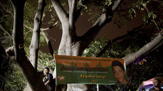 """In this June 1, 2013 photo, a banner showing a portrait of slain teen Ebed Jassiel Yanez Caceres hangs from a tree at a """"Justice for Life"""" concert, organized by people who say their family members were killed by security forces, in Tegucigalpa, Honduras. In the midst of a scandal over the police shooting of a university president's son, the government of Honduras launched an unprecedented effort last year to clean up a U.S.-backed police force widely seen as deeply brutal and corrupt. The banner reads in Spanish; """"Honduran military killed me during Operation Lighting. Where is the Justice? Assassins, abettors, instigators. We demand punishment now!"""" (AP Photo/Esteban Felix)"""