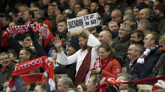 A Liverpool fan holds a sign during their English Premier League soccer match against Arsenal at Anfield in Liverpool