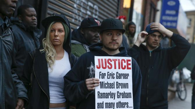 People stand next to a makeshift memorial where Eric Garner died during an arrest in July in Staten Island borough of New York