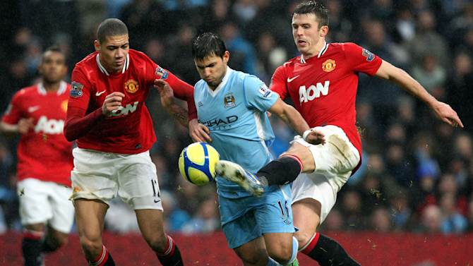 Manchester City's Sergio Aguero, center, vies for the ball with Manchester United's Chris Smalling, left, and Michael Carrick during their English FA Cup third round soccer match at the Etihad stadium, Manchester, England, Sunday, Jan. 8, 2012. (AP Photo/Scott Heppell)