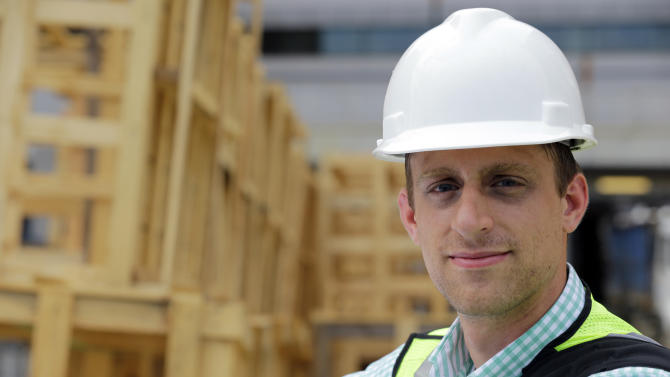 """Drew Miller, poses for a photograph, at a building under construction, Wednesday, July 10, 2013 in Silver Spring, Md. Miller quit a steady government contract job to take a chance on a company that's using """"smart technologies"""" to help big corporations cut lighting costs. (AP Photo/Alex Brandon)"""