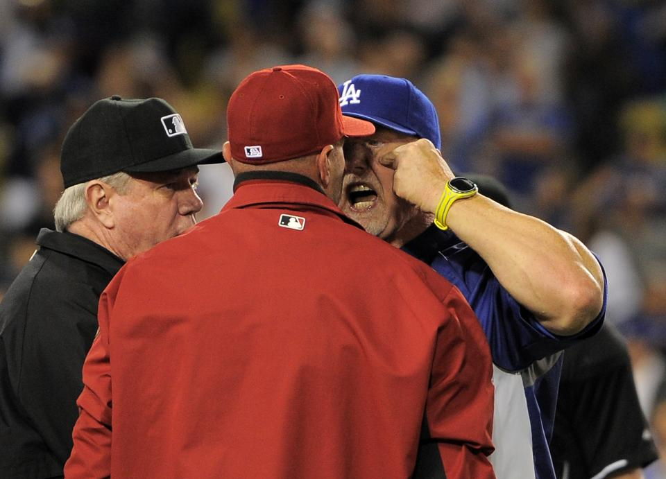 Los Angeles Dodgers batting coach Mark McGwire, right, yells at Arizona Diamondbacks manager Kirk Gibson after Los Angeles Dodgers' Zack Greinke was hit by a pitch during the seventh inning of their baseball game, Tuesday, June 11, 2013, in Los Angeles.  (AP Photo/Mark J. Terrill)