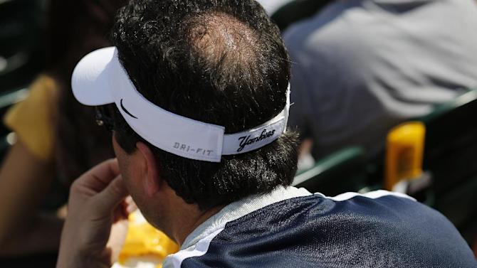 A fan of the New York Yankees watches a spring training exhibition baseball game against the Pittsburgh Pirates in Bradenton, Fla., Thursday, March 5, 2015. (AP Photo/Gene J. Puskar)