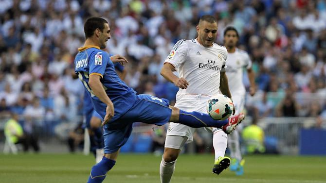 Real Madrid's Karim Benzema from France, right, in action with Getafe's Alvaro Arroyo, left, during a Spanish La Liga soccer match at the Santiago Bernabeu stadium in Madrid, Spain, Sunday, Sept. 22, 2013
