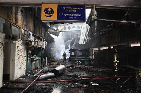 Fire fighters walk amid debris from fire at Jomo Kenyatta International Airport in Kenya's capital Nairobi