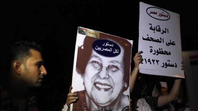 "Activists carry placards with a picture of Egyptian women's rights activist and writer Latifa al-Zayyat with Arabic that reads ""a constitution for all Egyptians, monitoring the newspapers was restricted in the 1923 constitution,"" during an anti Islamist dominated constitutional assembly protest in Cairo, Egypt, Tuesday, Oct. 2, 2012. Islamists are seeking to enshrine in Egypt's new constitution a number of articles that secularists and liberals fear would bring theocratic rule and severely set back civil liberties, including provisions empowering clerics to review laws and restricting women's rights. (AP Photo/Nasser Nasser)"