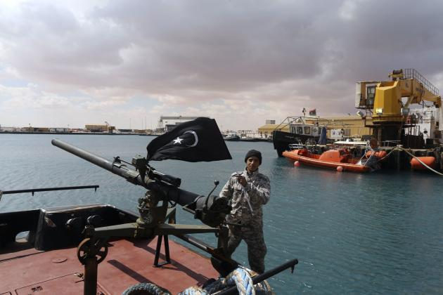 A rebel under Ibrahim Jathran holds the Cyrenaica flag while standing on a boat at Es Sider port in Ras Lanuf