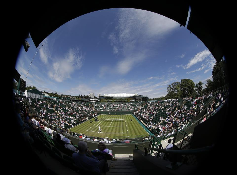 In this photo taken with a fisheye lens, Bernard Tomic of Australia serves to David Goffin of Belgium during a first round men's singles match at the All England Lawn Tennis Championships at Wimbledon, England, Tuesday, June 26, 2012. (AP Photo/Sang Tan)