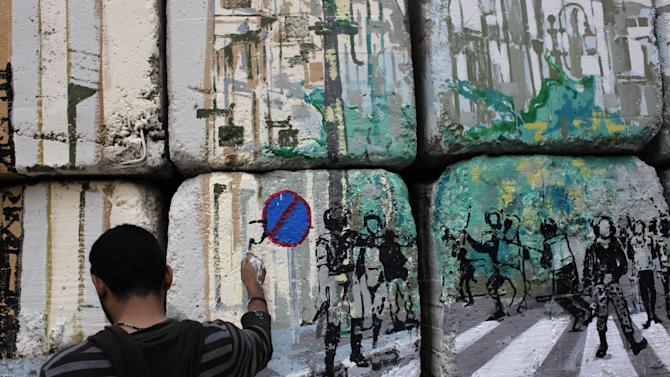 "In this Tuesday, March 13, 2012 photo, an Egyptian artist and activist works on the ""No Walls Street"" during the graffiti campaign to paint a reproduction of the streets behind them and targeted the concrete blocks walls in downtown Cairo, Egypt. After Egypt's ruling military sealed off streets around Cairo's Tahrir Square with walls of imposing concrete blocks, a group of artists decided to reopen the avenues on their own, in the public imagination, at least. (AP Photo/Nasser Nasser)"