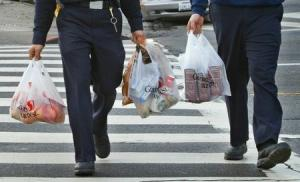 Firemen walk with plastic grocery bags in San Francisco