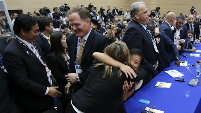 Members of International Wrestling federation react after the wrestling was announced one of the three candidate sports for the 2020 Olympics at the SportAccord International Convention in St.Petersburg, Russia, Wednesday, May 29, 2013. Three months after being dropped from the 2020 Olympics, wrestling won a reprieve Wednesday and made the IOC shortlist for inclusion in the games. Also making the cut were squash and a combined baseball-softball bid. (AP Photo/Dmitry Lovetsky)