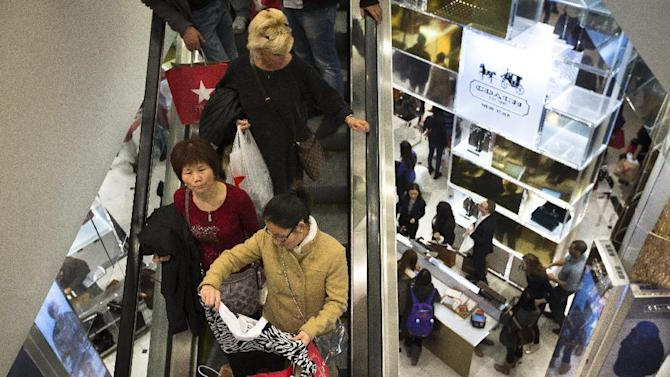 FILE - In this Nov. 28, 2013, file photo, shoppers descend on an escalator at the Macy's Herald Square store in New York. Macy's Inc. reports quarterly financial results before the market opens on Tuesday, Feb. 25, 2014. (AP Photo/John Minchillo, File)