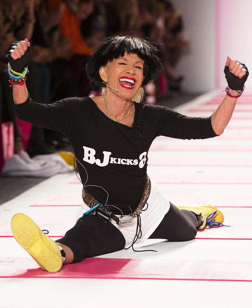 Designer Betsey Johnson greets the audience with her trademark cartwheel and split following a showing of her Fall 2013 collection during Fashion Week in New York, Monday, Feb. 11, 2013. (AP Photo/John Minchillo)