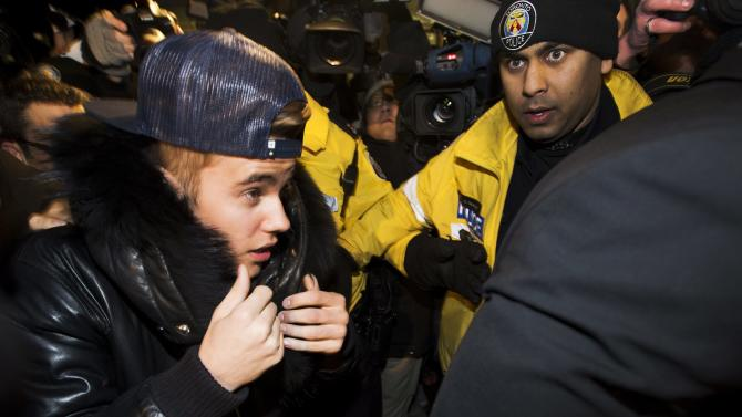 Canadian musician Justin Bieber is swarmed by media and police officers as he turns himself in to city police for an expected assault charge, in Toronto, on Wednesday, Jan. 29, 2014. A police official said the charge has to do with an alleged assault on a limo driver in December. (AP Photo/The Canadian Press, Nathan Denette)