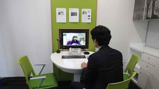 "In this Friday, Jan. 11, 2013 photo, customer Chung Yong-min does banking through a screen monitor connected to a video conference with bank employee Oh Ji-young, located in another office, at a Smart Banking Center in Seoul, South Korea. Standard Chartered is expanding its ""smart banking'' branches that employ a staff of three instead of eight. The company expects to have 30 more by the end of 2013. (AP Photo/Ahn Young-joon)"