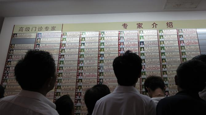 Patients look at the list of doctors at a hospital Friday, Aug. 24, 2012, in Shanghai. Despite an injection of more than $240 billion in government funding into health care over the past three years, the doctor-patient relationship has continued to break down. Doctors are overworked and underpaid, and many push drug sales or charge extra for services such as deliveries to make more money. Patients are faced with high medical expenses, brief consultations and often poor quality care. The anger built up over years is now exploding into violence, with doctors, nurses and interns around the country stabbed, punched or otherwise assaulted by patients or their relatives over the past year. (AP Photo)