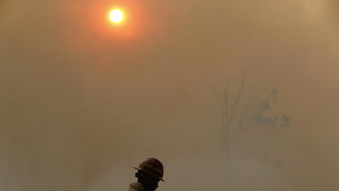 Smoke shrouds a firefighter as a bushfire burns above Cape Town's Tokai forest
