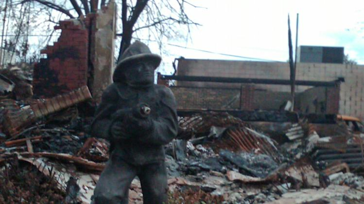 The charred remains of a firefighter statuette stands guard Friday Nov. 2, 2012 in front of a Belle Harbor house  that burned down during Superstorm Sandy. The fire spread to 14 houses on the same street, demolishing them and forcing frightened residents to flee the fire at the height of the storm. They used a surfboard and kayaks to ferry women, children and older people to safety. (AP Photo/Lawrence Neumeister)