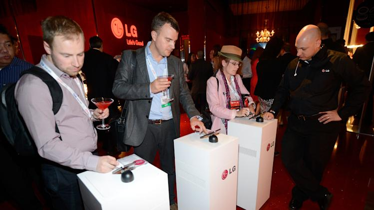 IMAGE DISTRIBUTED FOR LG - CTIA guests demo the new LG Optimus G Pro featuring Q Slide 2.0 at the Recharge, Refresh & Remix with LG Event at PURE NightClub, on Wednesday, May 22, 2013 in Las Vegas, Nevada. (Photo by Jeff Bottari/Invision for LG/AP Images)