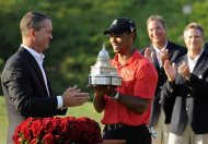 Tiger Woods, center, receives the trophy from Rob Forsyth, AT&T Mobility vice president and general manager, after winning the AT&T National golf tournament at Congressional Country Club in Bethesda, Md., Sunday, July 1, 2012. (AP Photo/Patrick Semansky)