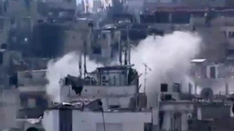 In this image taken from video obtained from the Shaam News Network, which has been authenticated based on its contents and other AP reporting, smoke rises from buildings due heavy shelling in Homs, Syria, on Monday, March 11, 2013. (AP Photo/Shaam News Network via AP video)