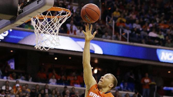 Syracuse guard Brandon Triche (20) heads towards the basket as Marquette guard Vander Blue (13) watches during the first half of the East Regional final in the NCAA men's college basketball tournament, Saturday, March 30, 2013, in Washington. (AP Photo/Alex Brandon)