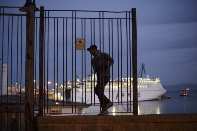 A Moroccan youth climbs along a wall overlooking Melilla harbour in Spain's north African enclave as a ship prepares to leave towards mainland Spain