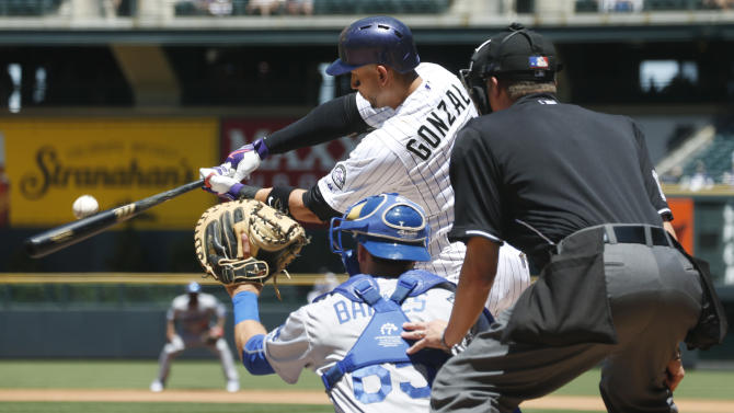 Colorado Rockies' Carlos Gonzalez, top, fouls off a pitch as Los Angeles Dodgers catcher Austin Barnes and home plate umpire Cory Blaser, right, look on during the first inning in the first baseball game of a doubleheader, Tuesday, June 2, 2015, in Denver. (AP Photo/David Zalubowski)