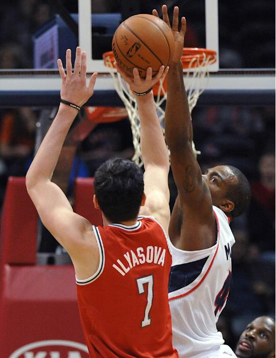 Milwaukee Bucks' Ersan Ilyasova (7) shoots over Atlanta Hawks forward Paul Millsap during the first half of an NBA basketball game Thursday, March 13, 2014, in Atlanta. Atlanta won 102-97