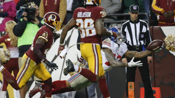 New York Giants wide receiver Odell Beckham (13) dives into the end zone for a touchdown as Washington Redskins cornerback Will Blackmon (41) and free safety Dashon Goldson (38) chase him during the second half of an NFL football game in Landover, Md., Sunday, Nov. 29, 2015. (AP Photo/Alex Brandon)