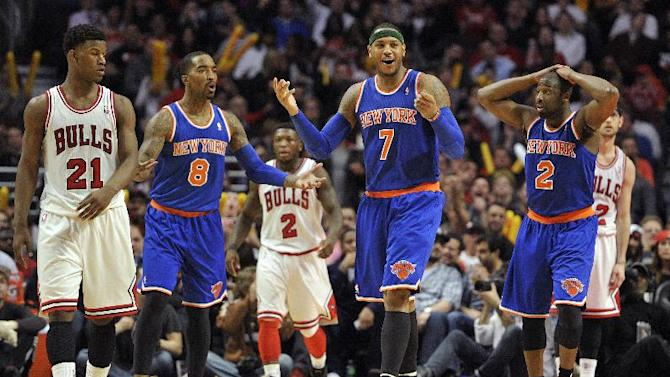 New York Knicks' J.R. Smith (8), Carmelo Anthony (7) and Raymond Felton (2) react to a play late in an NBA basketball game against the Chicago Bulls, Thursday, April 11, 2013, in Chicago. Bulls' Jimmy Butler (21), Nate Robinson (2) and Kirk Hinrich walk downcourt. The Bulls won 118-111 in overtime. (AP Photo/Jim Prisching)