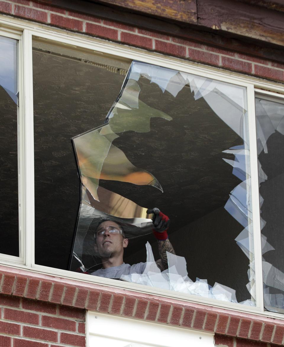 A worker with Belfor Property Restoration clears glass from a window as he works to board it up in the apartment of suspected Aurora movie theater gunman James Holmes, Wednesday, July 25, 2012, as residents were allowed back in the building, which had been closed off by police due to the continuing investigation of the shooting.(AP Photo/Ted S. Warren)