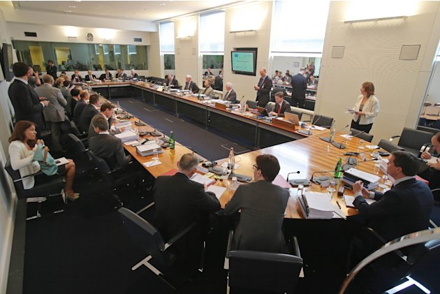 Participants sit around the table prior to the hearing at the FIA headquarters in Paris, Thursday, June 20, 2013. The hearing to determine whether Mercedes and Pirelli broke Formula One rules by holdi